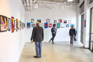 three people in a gallery space looking at artwork on a wall.