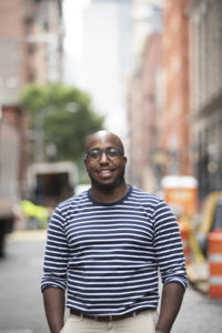 Image of Jerome Harris from the waist up in a stiped shirt, on a city street