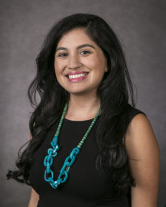 Portrait photograph of Mia Lopeza in a black top with a turquoise blue necklace
