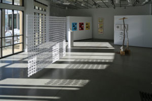 View of the exhibition in the gallery, with windows along the left side, light streaming in, and views of a few artworks
