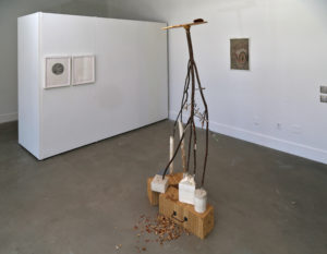 View of a tall sculpture made from branches as legs, on plywood boxes. There is a framed drawing of an eye opposite the sculpture.