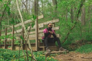 Photo of man sitting on a wooden bridge in the woods