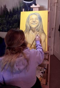 """Halle Luttrell painting a portrait from her color series called, """"Rusty"""", 2021, oil on canvas."""