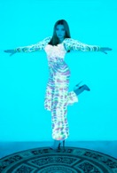 photo of a woman standing on one leg, the other kicked out behind her, against a bright blue background