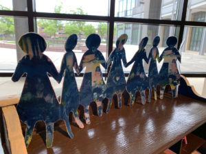 Photograph of an artwork that consists of a chain of paper dolls made from cyanotype images