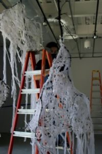 Image of sculpture consisting of large branches wrapped with white fabric, hanging from the gallery ceiling