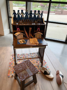 Image of an artwork that consists of a child's desk, with a small stool, a handmade rug, and handmade books and constructions
